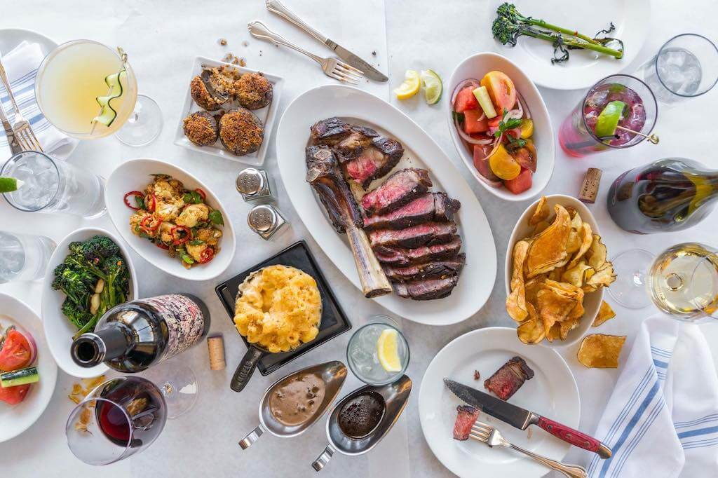 table full of food with large steak in center where to eat in Summerlin