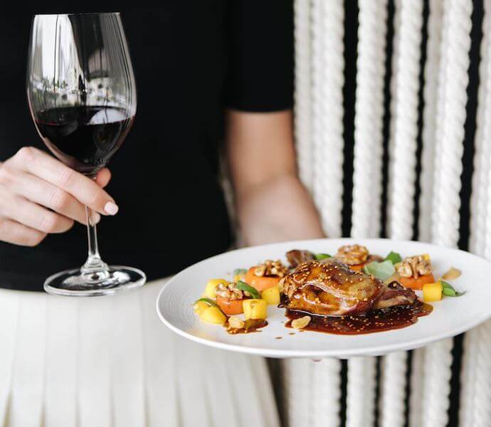 roasted chicken with vegetables and a glass of wine