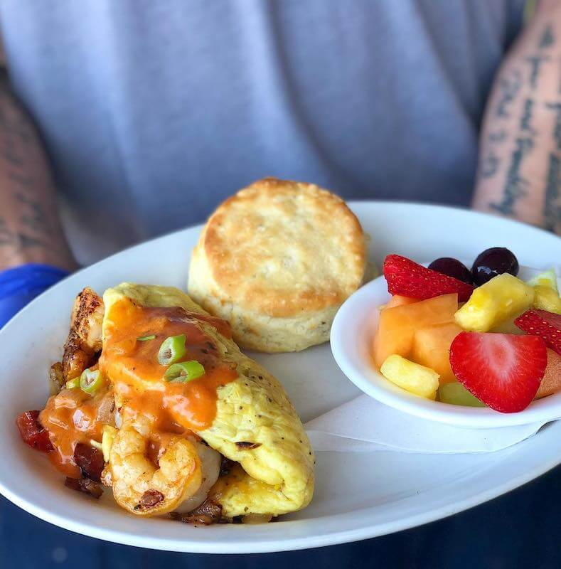 omelet with fresh fruit and a biscuit