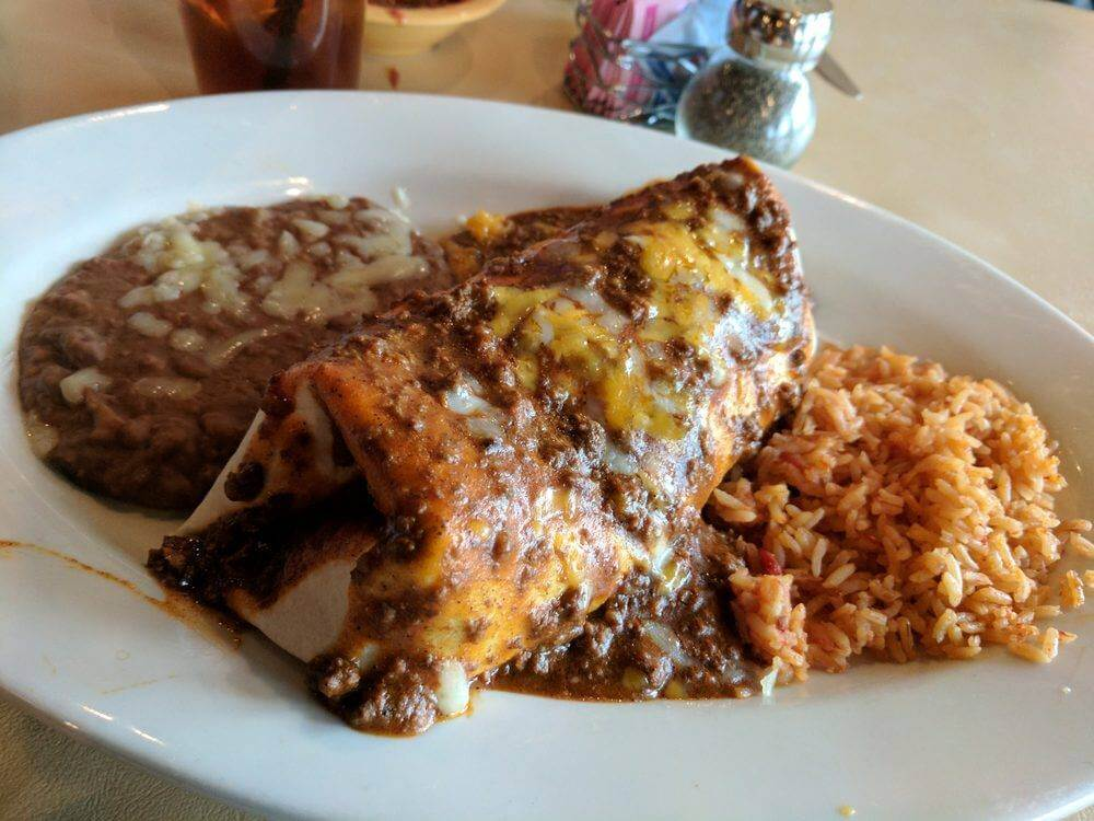 burrito topped with chili with beans and rice
