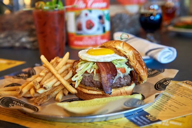 bacon burger with fried egg on top and a side of fries