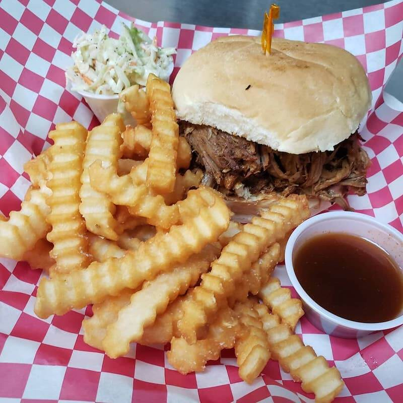 brisket sandwich with fries and sauces