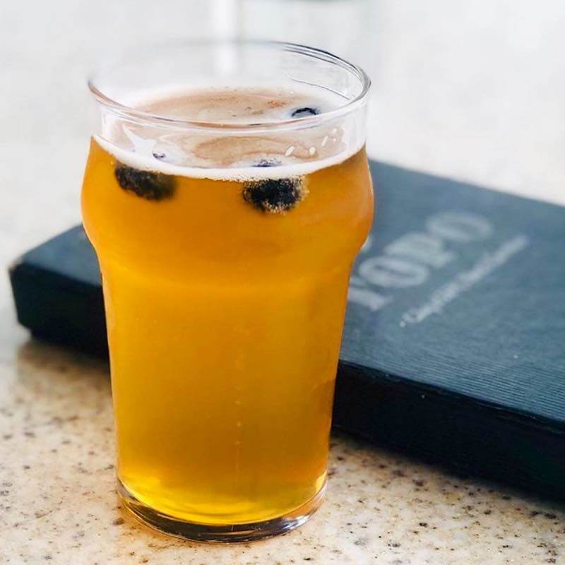 glass of craft beer with blueberries floating in it