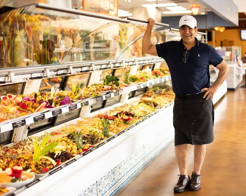 man standing in front of display case full of food
