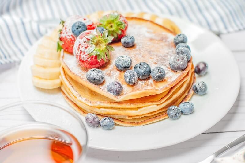 pancake topped with blueberries, bananas and strawberries