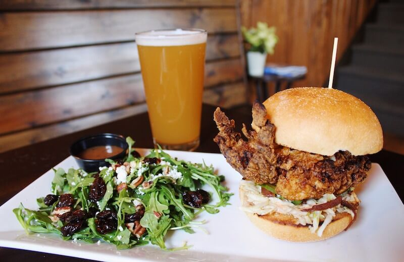 fried soft shell crab sandwich with a beer and salad