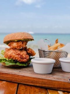 fried chicken sandwich and beer in front of ocean