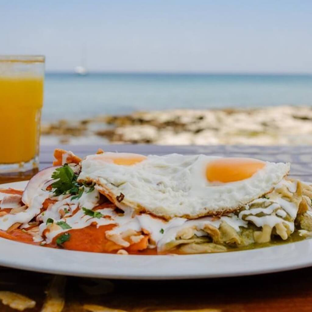 breakfast plate with juice in front of ocean view in Cozumel