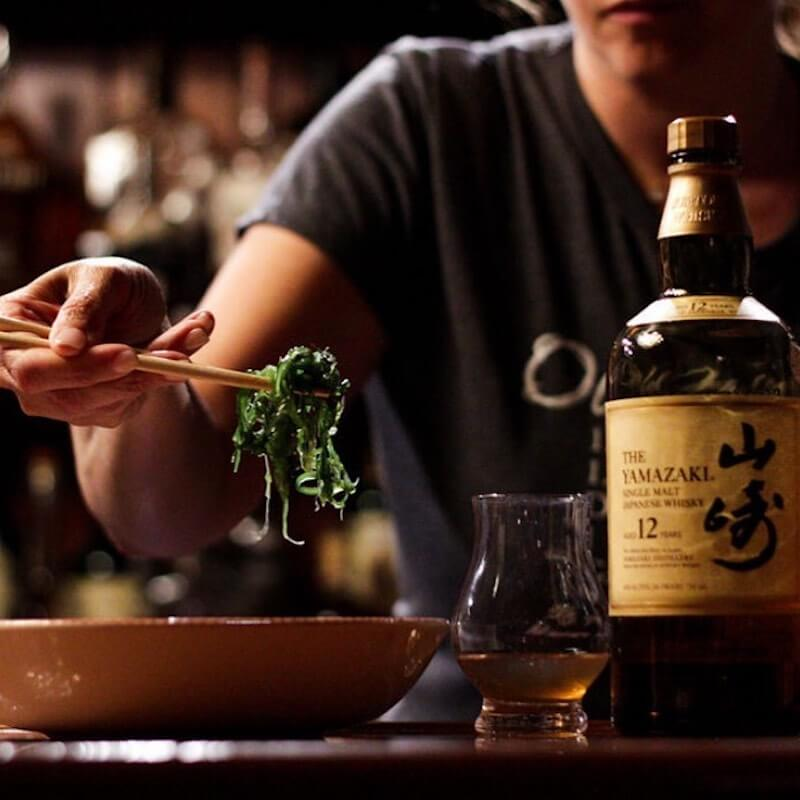 bartender with Japanese dish and bottle of Japanese whisky