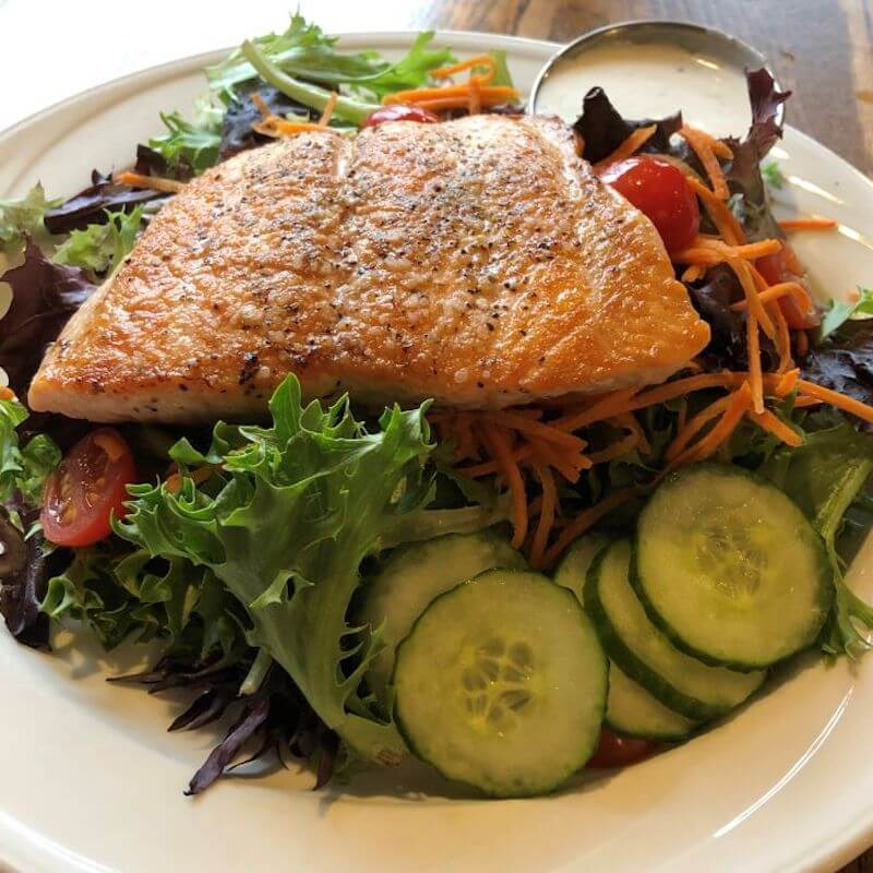 grilled salmon atop a salad