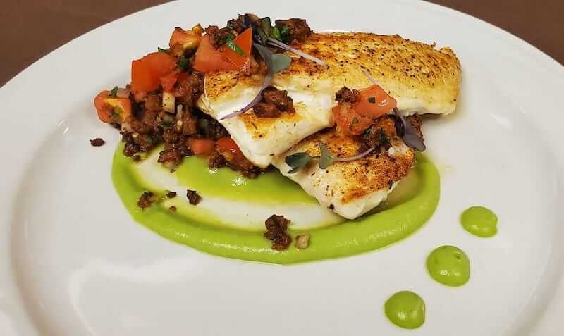 roasted fish on a plate with a green cream sauce