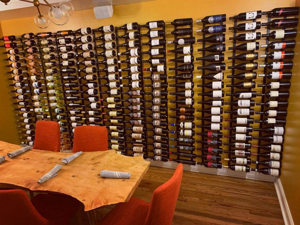 dining room with a wall full of wine on a rack