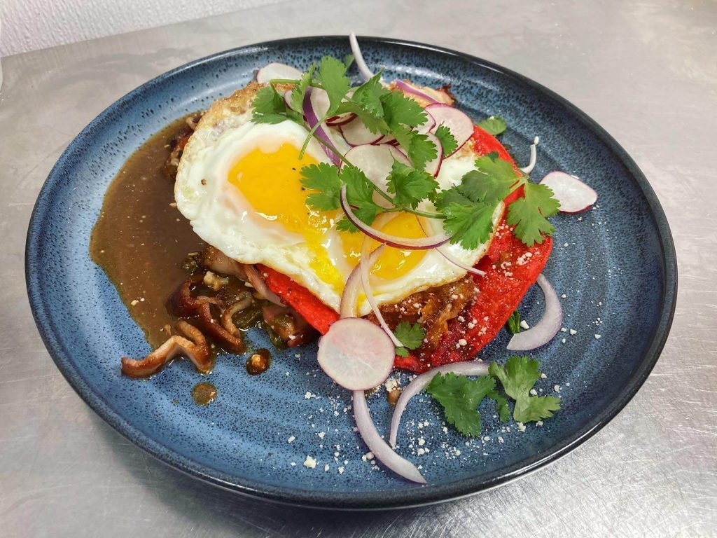 plate of chilaquiles topped with egg