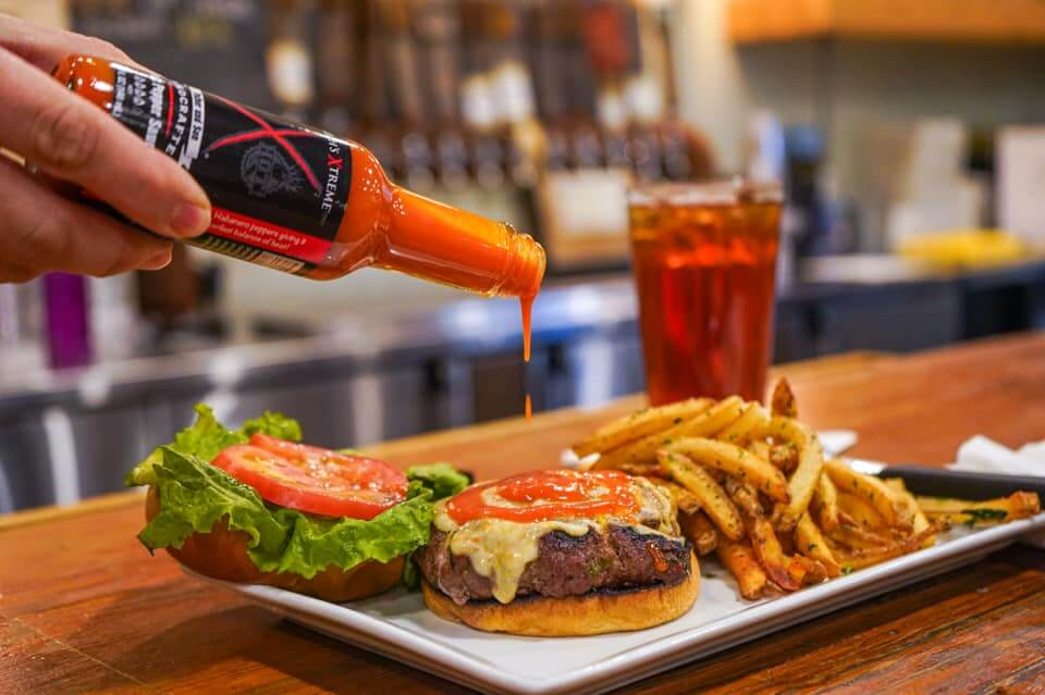 hot sauce being poured on a burger with a bar in the background