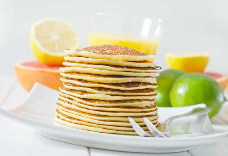 stack of pancakes on a plate with fruit