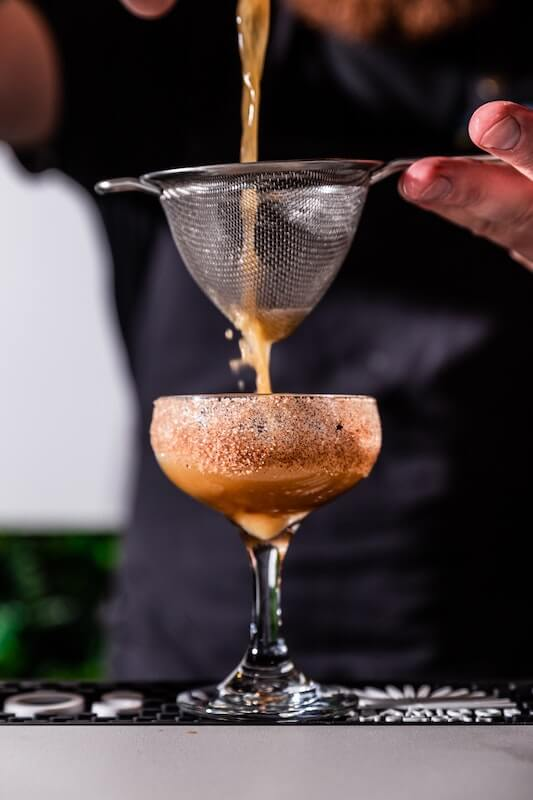 coffee cocktail being poured through a strainer